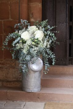 rustic flowers in milk churn