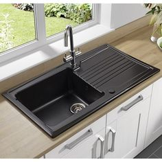This black satin ceramic sink has lots of personality and style. The Astracast Equinox ceramic 1 bowl sink offers a contemporary twist on a very functional fixture. Ceramic Kitchen Sinks, Steel Kitchen Sink, Kitchen Tiles, Black Sink, White Cupboards, New Countertops, Kitchen Decor Themes, New Kitchen Cabinets, Kitchens