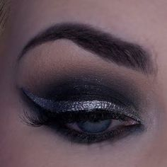 This silver eye liner behind a dark smokey eye will give you an unforgettable look. A video tutorial shows how to get a silver smokey cat eye like you've never seen before.