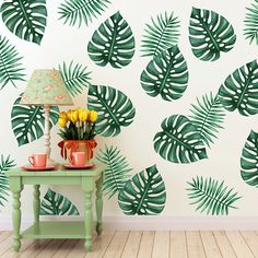 Large green palm branch wall decals featuring two major design patterns, one with thicker vinyl palm leaves and another with thinner leaves. The decals are placed on a white wall evenly spaced as a pattern behind a green table with a lamp and an orange pot.