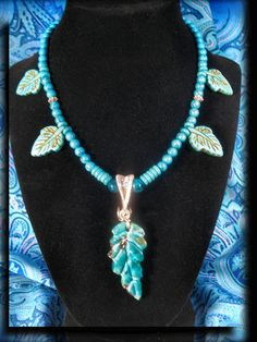 Hand Carved Chrysocolla Pendant In Silver Wire Wrap And Turquoise Beaded Designer Choker Necklace 10041  The pendant is chrysocolla and the