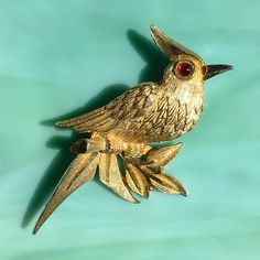 This vintage 1970s signed BSK (1948 - mid-1980s) gold-tone cardinal pin / brooch is perched on a leafy branch. With beautifully detailed wings, long tail, bright red glass eye, and a pert tuft on his head, he appears quite life-like. Hes in fantastic vintage condition and would make the perfect gift for your favorite bird enthusiast as a whimsical touch to a lapel, purse, scarf, or hat. The Audubon Society says one of our most popular birds, the Cardinal is the official state bird of n...