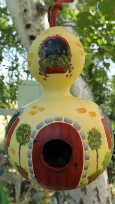 This gourd birdhouse was sealed and painted several times with a creamy yellow. The cottage has red shutters, window boxes and door with flowers