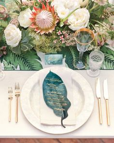 Menus handwritten in gold ink on oversize die-cut palm fronds served as menus and played off the patterned runners. Each table was set with centerpieces of white roses and local foliage and blooms, including king proteas, photinias, and kupukupu ferns.