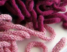 Knit I cord with an Inox machine,(Embellish-knit machine breaks),then felt or use 2 strands of wool with an I hook and crochet a chain.