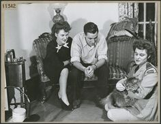 Member of the Canadian Women's Army Corps holding a cat next to young man and woman seated on couch, 1944. Source: Library and Archives Canada.