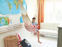 """This family's homeschool is located in a loft above the kitchen. Homeowner and photographer Julie Ranee purchased the hammock on a trip to Ecuador 22 years ago. """"I've been carting the hammock around for so long and now I've finally put it to good use. The kids love having a new and relaxing reading nook,"""" says Ranee."""