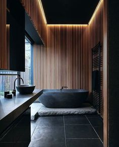 a Japandi bathroom with black and light colored wood is highlighted with a natural stone slab and countertop