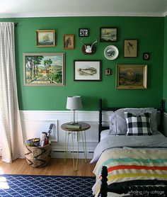Boy's vintage-style bedroom with walls painted Benjamin Moore Bunker Hill Green (Whaling City Cottage)