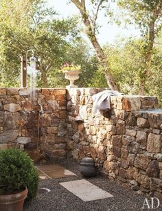 Off the master bedroom is an outdoor shower walled with stone salvaged when digging the foundations of the house | archdigest.com