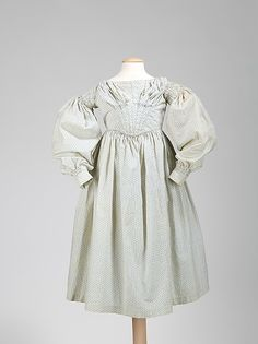 1837-1840 child's dress, American. It is charming to see period dresses produced in miniature sizes for children, and the dress shown is a very high-style garment. It is a perfect example showing the collapse of the gigot sleeve in 1837 and the beginning of the V-shaped form of bodice in the 1840s. Additionally, the puffing over the bust adds another adult dimension.
