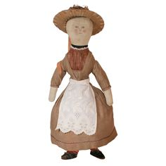 """Charming, homemade cloth doll with naively drawn ink features, wearing a brown cotton dress with feather-stitched ornamentation and a red satin insert in bodice, a white apron,and hand-knitted stockings. Many layers of petticoats and a straw hat. Clothing all original. Leather shoes are of the period, but not original to the doll. Ex. Collection Madeline O. Merrill. Illustrated: """"The Art of Dolls 1700-1940"""" by Madeline Osborne Merrill, page 142. $7800.00"""