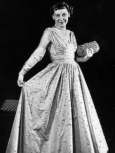 "Mamie Eisenhower  ""First Lady pink"" became a national sensation following Mrs. Eisenhower's 1953 debut in a peau de soie Nettie Rosenstein design with 2,000 rhinestones. Matching evening gloves and a pearl-encrusted clutch finished the look."