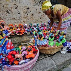 Una ragazza vende bambole colorate di stoffa nel centro della città vecchia #lavana #cuba