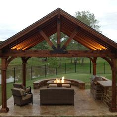 A fireplace pavilion made using the Truss Base Fan, Truss Accents, and Post to Beam Bolt Brackets by OZCO Ornamental Wood Ties
