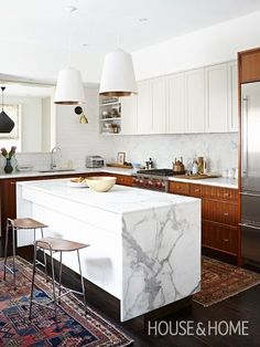 a renovated kitchen retains original upper cabinetry painted a soft gray and pairs it with new walnut lower cabinetry