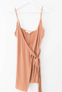 Simplistic dress with a wrap front and adjustable waist tie. Frayed hem. Non-stretch woven material. 100% Tencel Imported