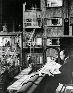 Alfred Hitchcock, director of Rear Window in 1954, reads a newspaper while waiting on the set.
