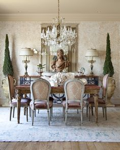 Gilded antique lamps flank a terracotta bust. Floors are reclaimed wood. Wallpaper is by David Goldberg Design.