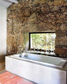 The mix of natural stone wall with modern simple white lines of the bathtub gives this space a very unique look. It works well together!