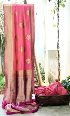 ORANGE IRIDESCENT PINK BENERAS SILK HAS FLORAL BUTTAS ALL OVER. THE SAREE HAS INTRICATELY WOVEN ZOLD ZARI BORDER AND PALLU GIVES THE SAREE A RAVISHED LOOK.