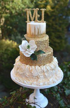 Gold wedding cake with sugar magnolia.
