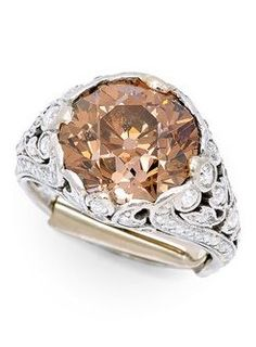 An Antique Coloured Diamond Ring, circa 1910. Centring an old European-cut brown diamond weighing approximately 4.75 carats, to elaborate diamond-set shoulders and gallery pierced with floral, foliate and vine motifs, mounted in platinum.