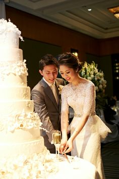 The tiered wedding cake is cut by the bride and groom in the ballroom of Four Seasons Hotel Sydney. Photo: Blumenthal Photography.