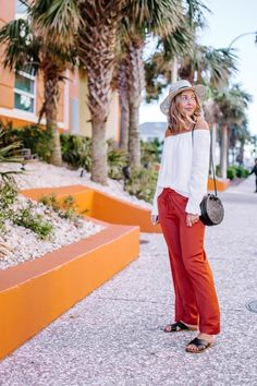 Orange pants outfit for a casual beach outfit | vacation outfit | white off the shoulder top | black straw bag | straw fedora | flat black sandals | casual spring outfit