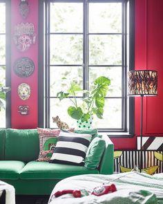El sofá verde y las máscaras de la pared aportan un toque personal a este dormitorio