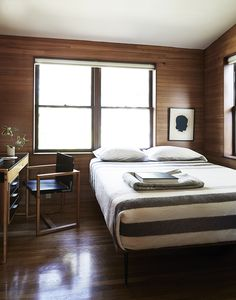 The rooms, featuring sloped ceilings, feel small and intimate. In the guest bedroom, there is a custom bed and a Swedish school desk found on eBay.