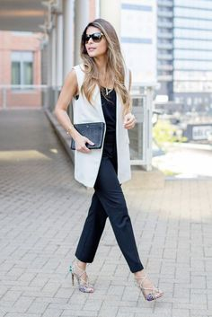 a black jumpsuit, a blush vest and colorful shoes
