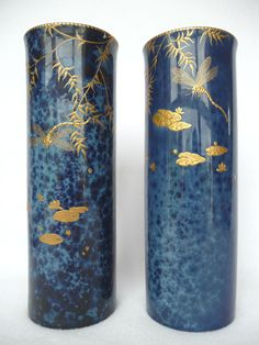 A Matched Pair of Royal Doulton Titanian Ware Vases, by Robert Allen, of cylindrical design, gilded with dragon flies, branches and lily pads, on a blue ground, printed factory mark, stamped 1361/A, painted RA 9390, 26cm and 25.5cm