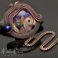 A beautiful purple ripple bead by Darcy York of Silver Gypsy features blue and pink swirls with a pale purple base. The pendant, measuring 5cm in length, features many yards of hand wrapped and woven copper wire. A lustrous blue freshwater pearl accents the finished design, which will arrive with...