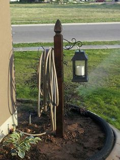 Lantern & Hose Holder from a wooden post. Love it!
