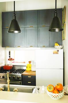 Amazing renter's kitchen renovation. Love the soot-colored cabinets and the gold pulls and faucet - via Little Green Notebook