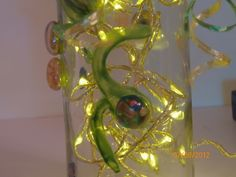 Zoom shot of glass gem ladybug on side of dragonfly bottle