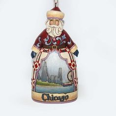 "Heartwood Creek by Jim Shore  CHICAGO SANTA ORNAMENT    New collection from Jim Shore is whimsical tribute to the great cities of America. The Chicago Santa features the Second City skyline including the Ferris Wheel at Navy Pier. The quilt pattern on Santa's robe is called Chicago Star.    Size: 4.5""H x 1.75""W x 2.35""L  Materials: Stone Resin"