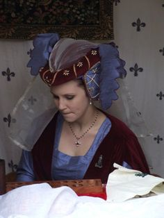 c.1405-1470 Burgundy Velvet and Blue Silk Heart Shaped Hennin, with Cream Pearls and Red Jewels and a Cream Veil. Blue Silk Dagging finishes the look ba...