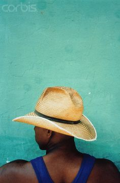 Cuban wearing straw hat in front of green wall