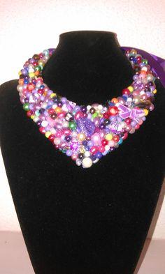 Collar baberos, en diferentes tonalidades predominando los colores morados y malvas