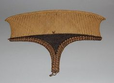 Fan made of very finely plaited fibre. It is of shallow shovel shape. the handle and lower edges are completely bound with pale fibre and human hair so as to form a series of alternating pale and dark triangles. The lower part of the fan is also inwoven with dark sinnet.