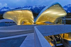 Architect Zaha Hadid first made her mark on Austria's Innsbruck region with the 2002 Bergisel ski-jump tower. She returned with this design for the Nordpark Cable Railway, a four-station funicular line that replaced a 100-year-old tram and transports passengers up a vertiginous incline for 1.1 miles. Each of Hadid's stations is capped with swooping glass shapes that suggest ice floes and snowdrifts. Here, a view of Hungerburg Station, the final stop in the funicular's ascent which was…