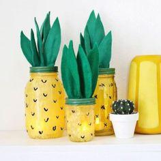 des bocaux en verre peint en jaune à pois noirs et feuilles en papier vert
