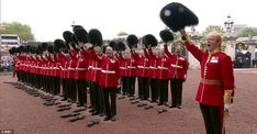 Guardsman line up and salute the Queen earlier today as she arrives at Buckingham Palace