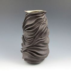 This handmade sculptural ceramic pottery vessel is thrown on the potters wheel.  I have thrown it with thick walls to allow for deep carving.  I wait until a certain degree of drying has occurred and then I carve and manipulate the chocolate brown stoneware clay by hand.  I do not add any additional clay, I only subtract.  The piece is bisque fired in my electric kiln and then glazed a semi matte cream on the interior of the vessel and the recessed bottom of the foot only.  The outside is…