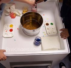 Colored water & eye droppers. Children mix primary-colored water to make secondary colors. The bucket in the middle is for dumping the water when finished, or to start over. A