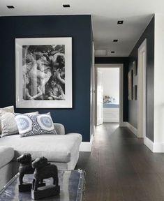 salon bleu petrole dans un style art déco avec des meubles blancs et grand tableau au cadre noir au mur représentant des femmes en divers états