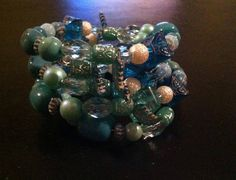 Dark Green, Clear, Off White, Light Green, Dark Blue, Dark Grey, and Blue Green Large Memory Wire Bracelet. Please visit my facebook page called The Pelican By Kristin Margarite. https://www.facebook.com/ThePelicanbyKristin/?ref=aymt_homepage_pane