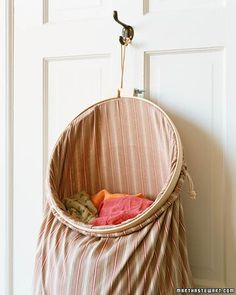 A hanging laundry bag saves floor space, but you have to wrestle with the drawstring to deposit dirty clothes. Have it both ways when you prop open the suspended bag with a large embroidery hoop at least 14 inches in diameter.